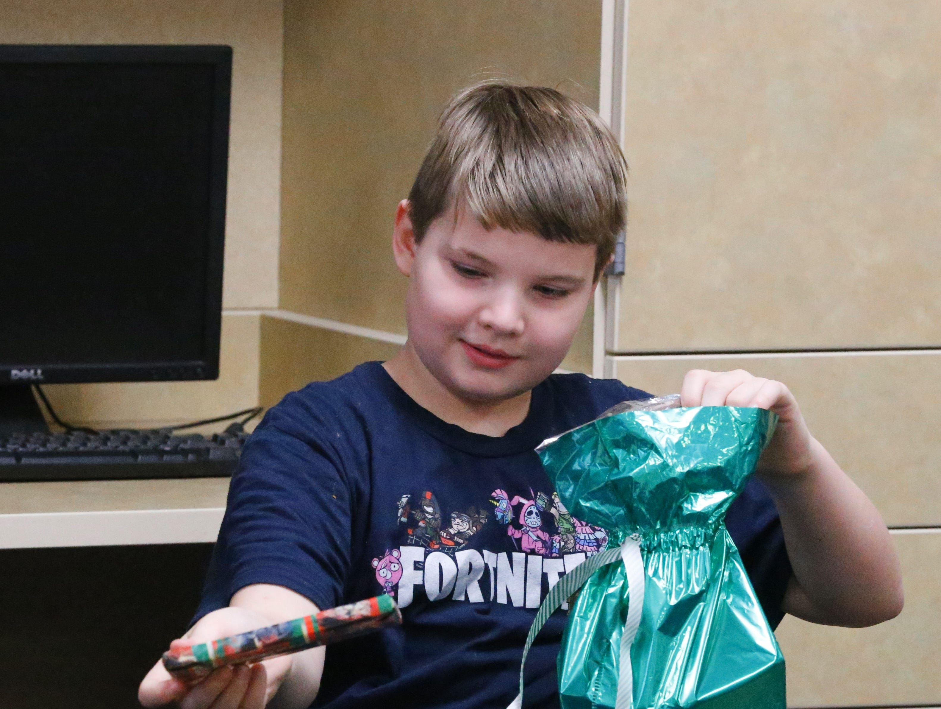 Joshua Idle, a fourth-grader at Fairview Elementary School in Richmond, opens a gift Jan. 7, 2019. Joshua and his younger brother, Ryan, were surprised with an Xbox One S purchased by Joshua's classmates with money raised from a store created by classmates Javeonte Johnson and D. J. Allen, who sold pictures to raise money for Idle. Idle was involved in an accident and lost his mom in Dec. 2018.