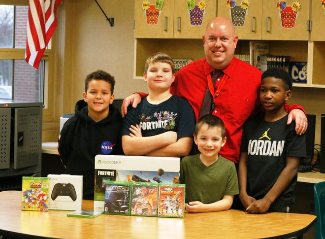 """Javeonte Johnson, left, and D. J. Allen, right, fourth graders at Fairview Elementary, came together to create the """"Josh Squad"""" a 'store' that draws and sells pictures to raise money for an Xbox One S for classmate Joshua Idle, second from left, and his younger brother Ryan. Joshua and Ryan were involved in a car accident and lost their mom in Dec. 2018. Also pictured is fourth-grade teacher Jim Jeffries, who oversaw the project."""