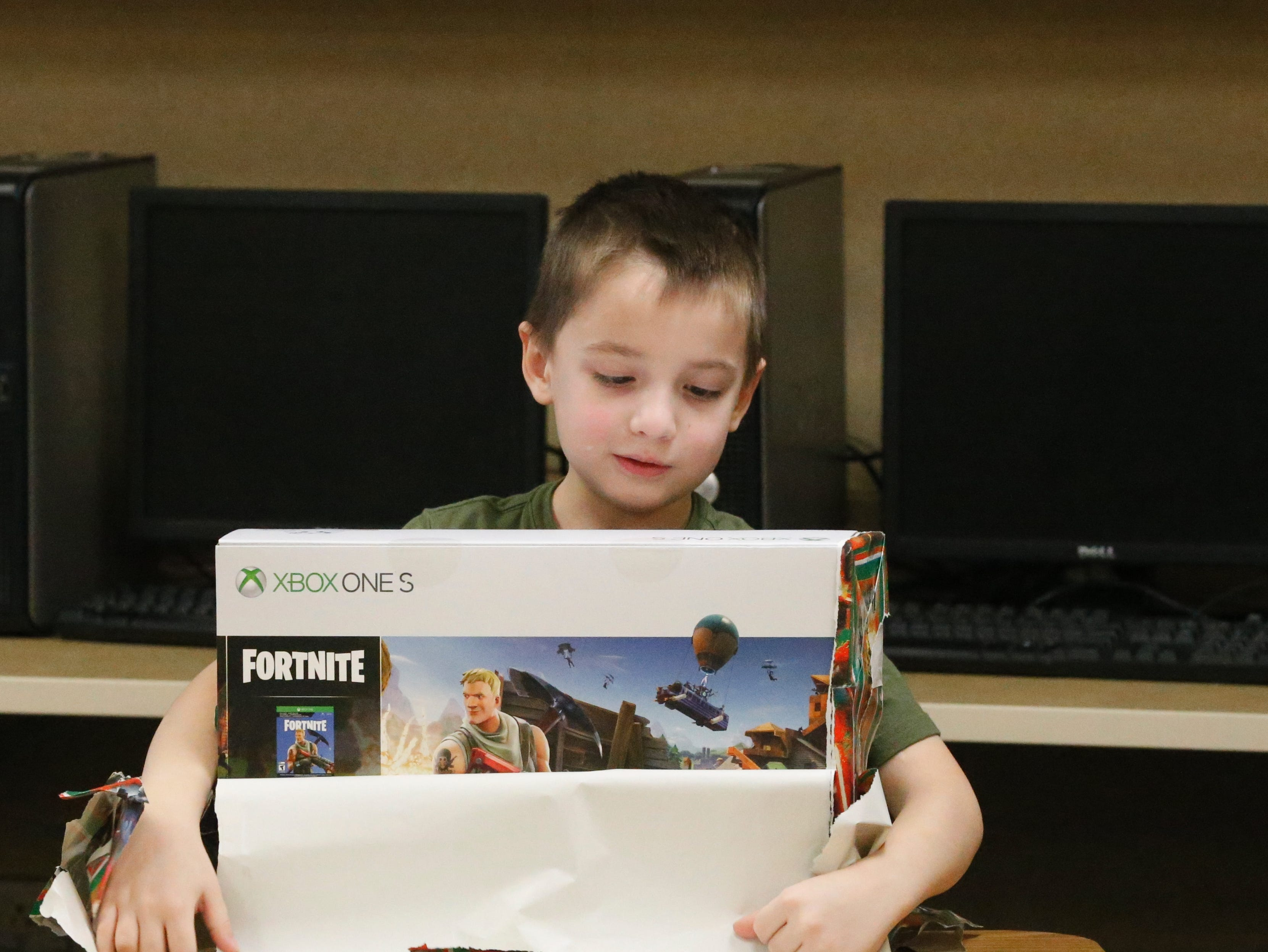 Ryan Idle, a kindergartner at Fairview Elementary School in Richmond, opens a gift Jan. 7, 2019. Ryan and his older brother, Joshua, were surprised with an Xbox One S purchased by Joshua's classmates with money raised from a store created by Javeonte Johnson and D. J. Allen, who sold pictures to raise money for Idle. Idle was involved in an accident and lost his mom in Dec. 2018.