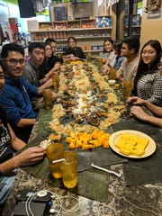 """A table of RIT students get ready for a """"boodle fight"""" at Casa Merlita in Gates."""