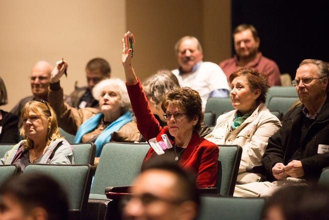 Some community members raise their hands after a health care question from Sen. Ron Wyden during a Marion County town hall at Woodburn High School on Monday, Jan. 7, 2019.