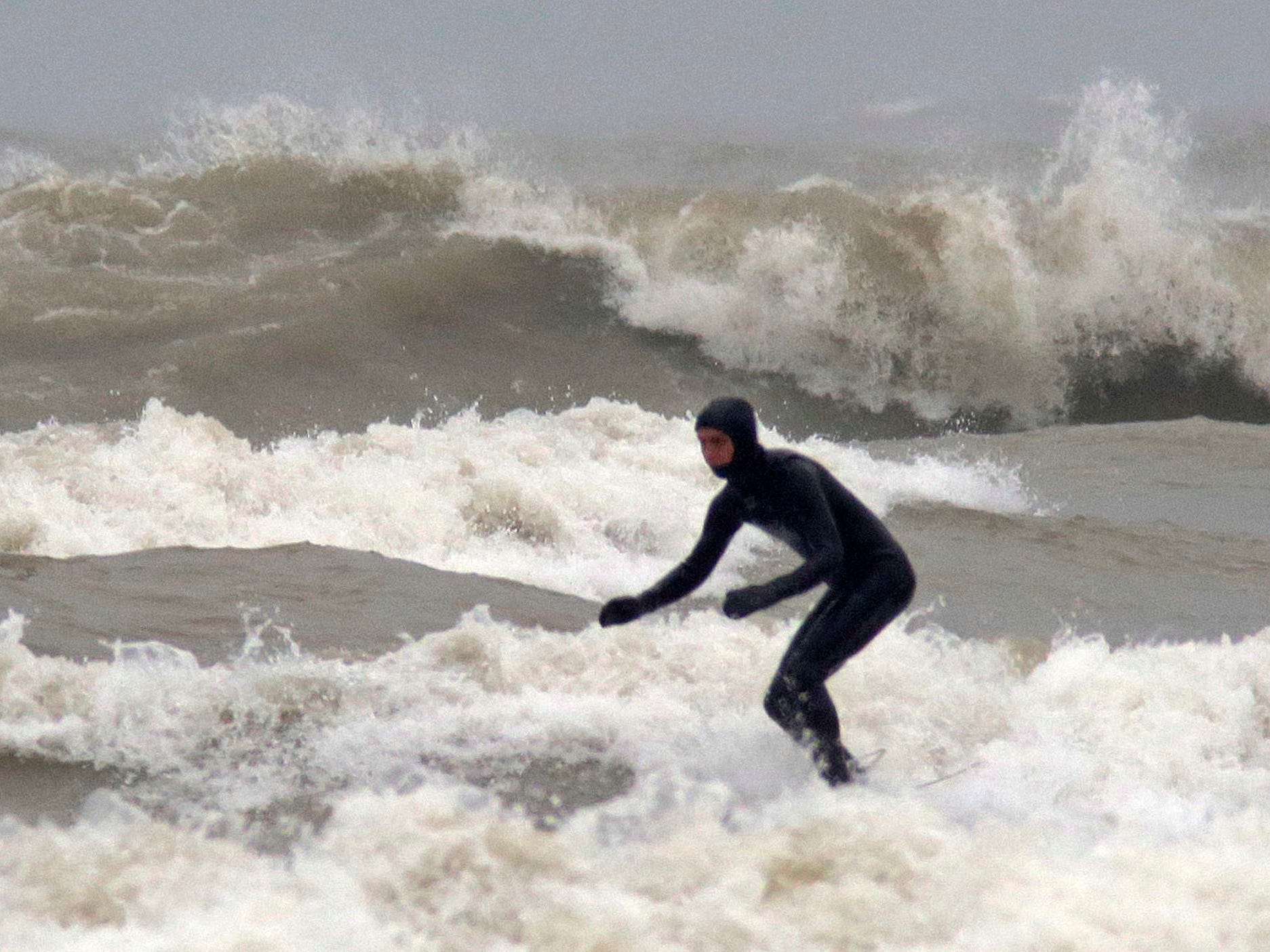 A surfer takes on the waves at Deland Park, Monday, January 7, 2019, in Sheboygan, Wis. Westerly winds of 15-25 knots were expected to be in the 3 to 8 foot range with possibilities as high as 10 feet.