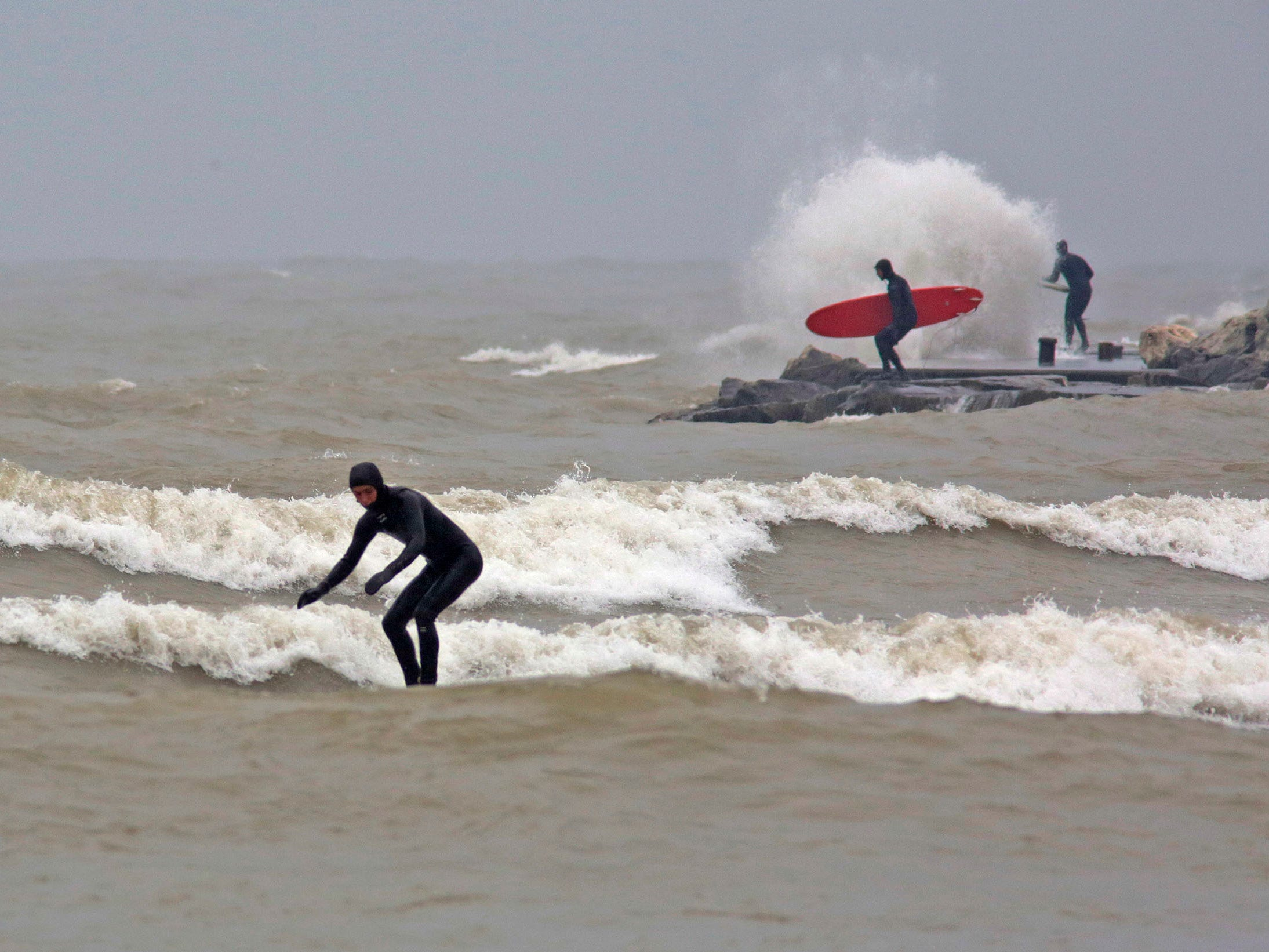 Surfers take on waves at Deland Park, Monday, January 7, 2019, in Sheboygan, Wis. Westerly winds of 15-25 knots were expected to be in the 3 to 8 foot range with possibilities as high as 10 feet.
