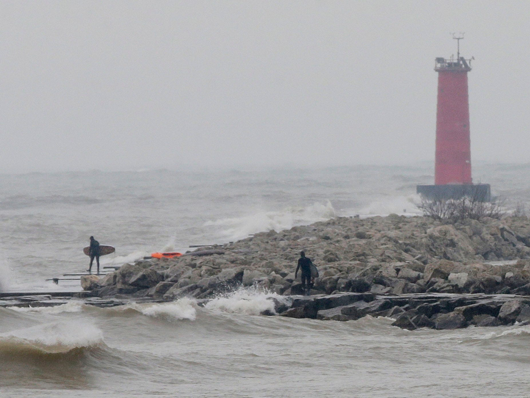 With the Sheboygan lighthouse holding firm, surfers take on waves at Deland Park, Monday, January 7, 2019, in Sheboygan, Wis. Westerly winds of 15-25 knots were expected to be in the 3 to 8 foot range with possibilities as high as 10 feet.