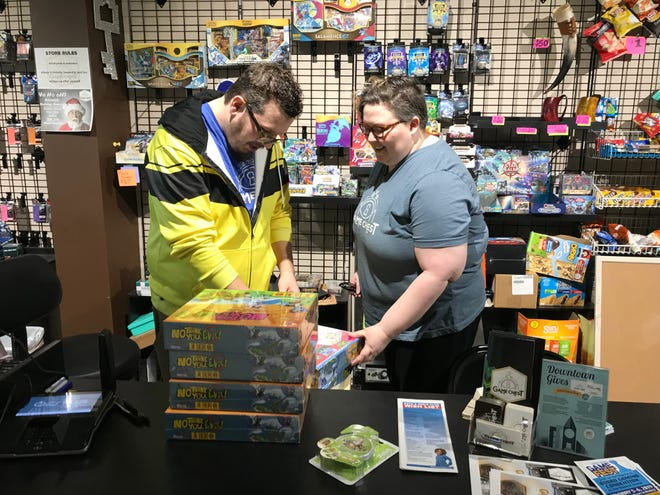 Ben and Amanda Wermers go through new arrivals to add to their business' inventory of board games. The Wermers own Game Chest in downtown Sioux Falls.