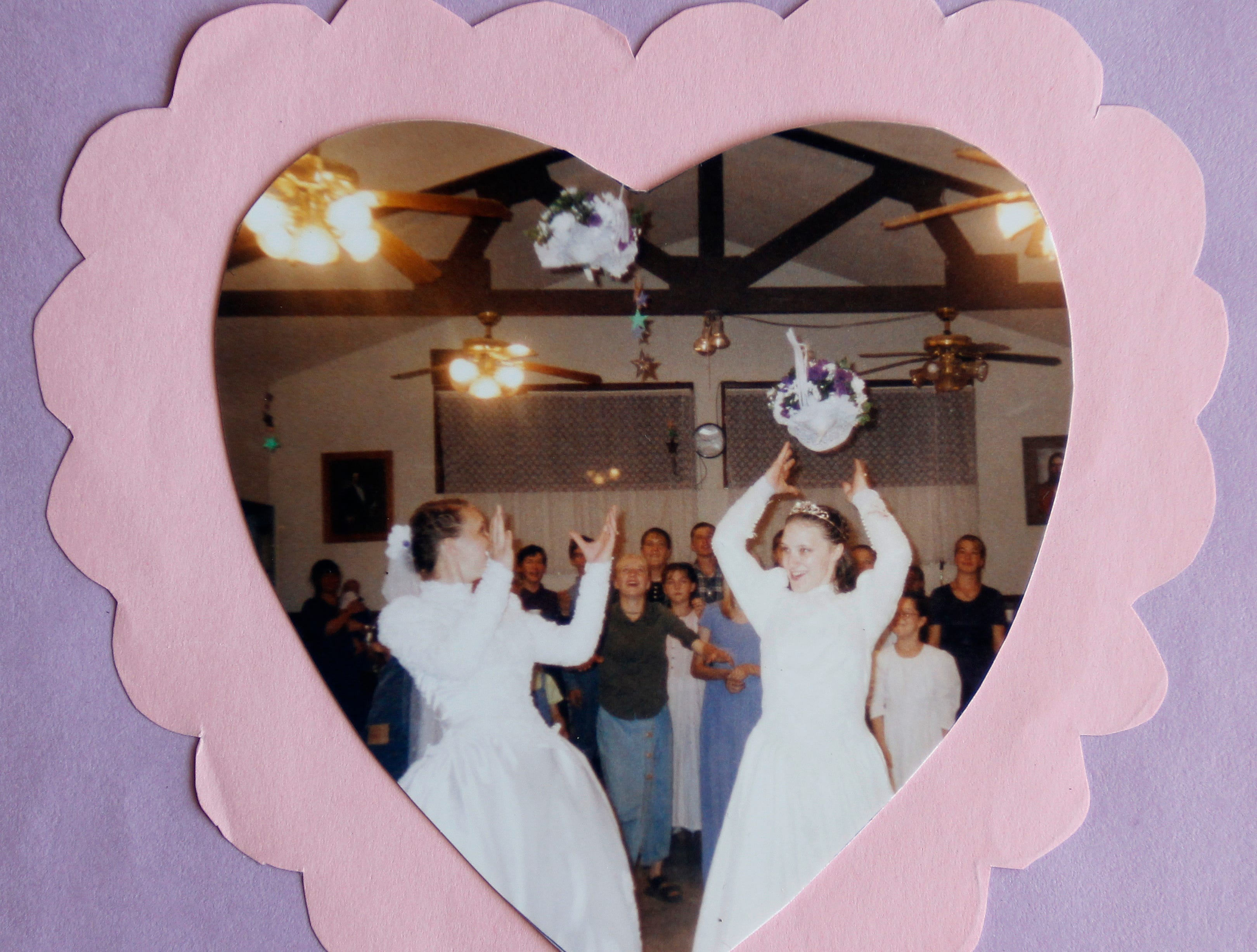 Sara and Heather Staples toss their bouquets in a photo from their June 2001 wedding to Charles Laub.