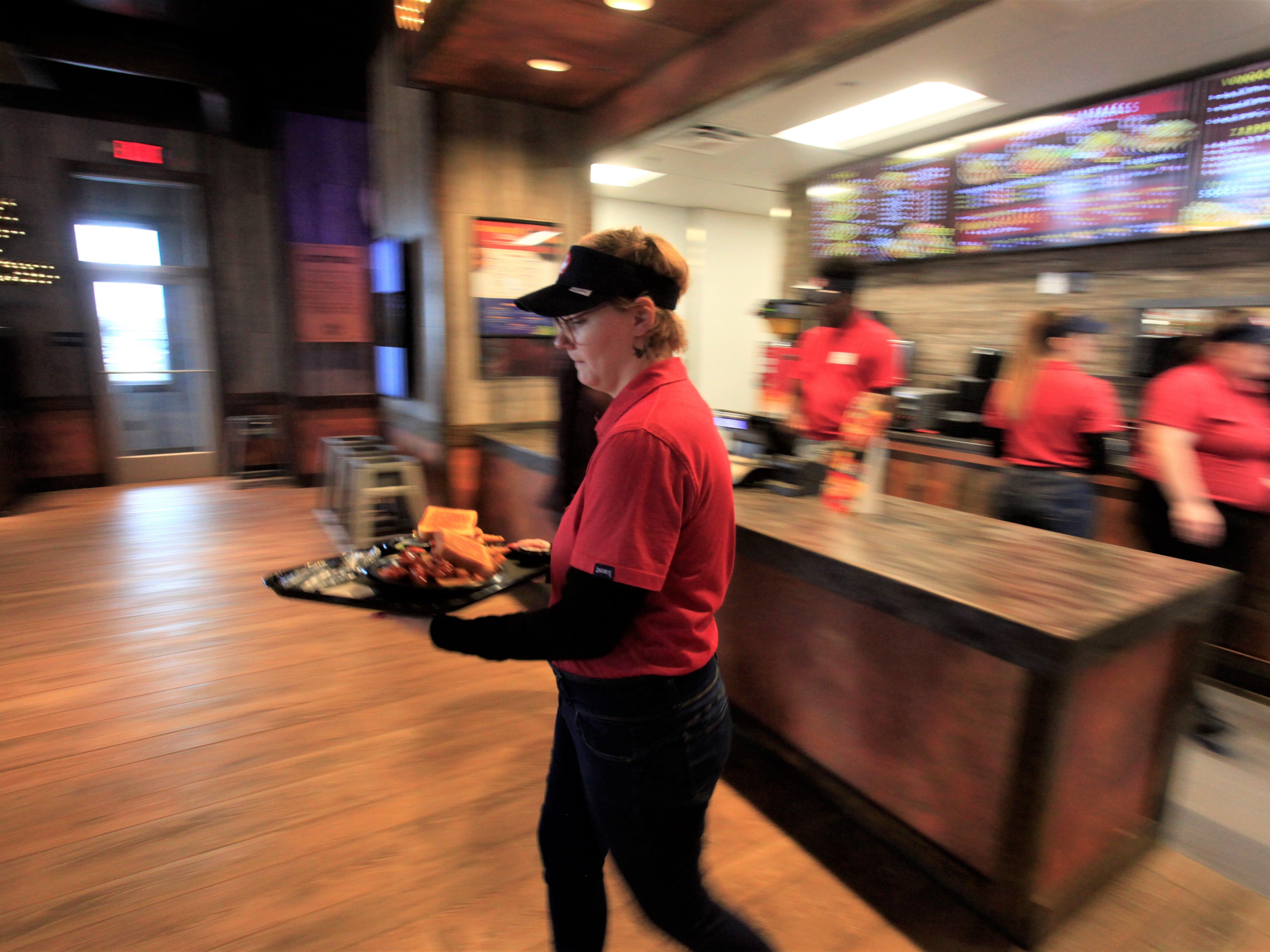 Karen Aguirre serves food at Zaxby's.