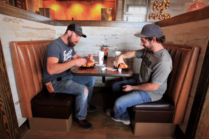 Brent Perryman, left, and Jacob Hall eat lunch during the first day Zaxby's is open at 540 W. El Camino Alto Drive in Springfield.