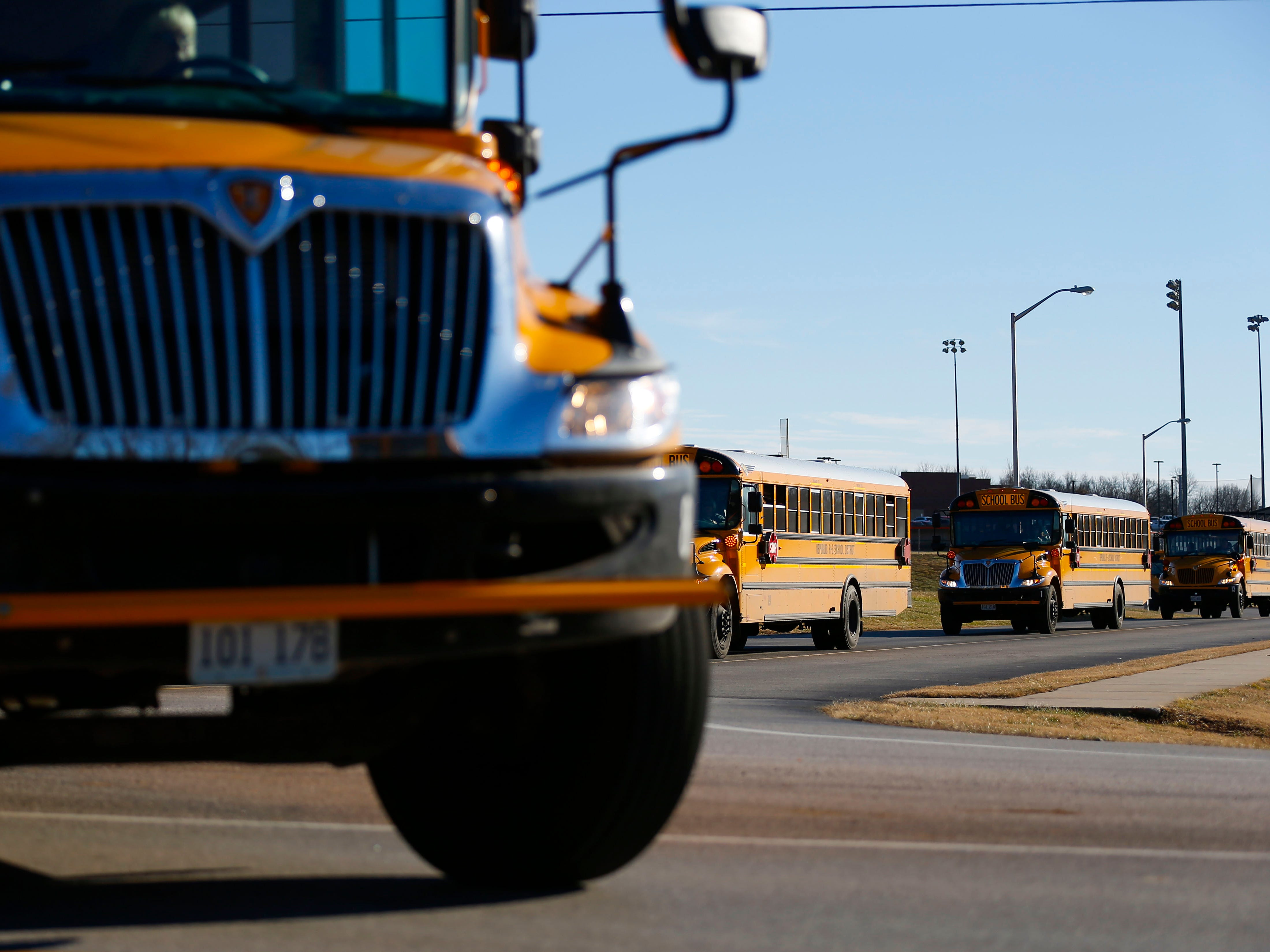 School buses make a left turn onto M Highway from Republic High School on Monday, Jan. 7, 2019. Construction of a one-lane roundabout to ease traffic and improve safety has begun at the intersection.