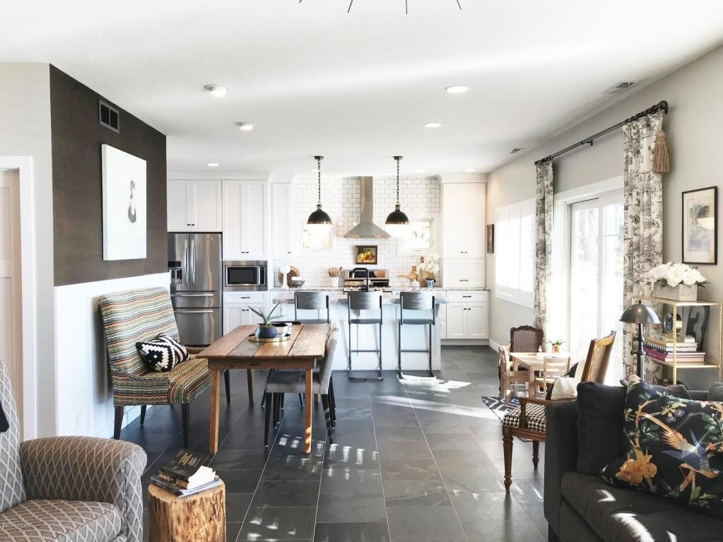 The sharp, distinctive kitchen features granite countertops, a large stainless steel farmer sink and custom white kitchen cabinets.
