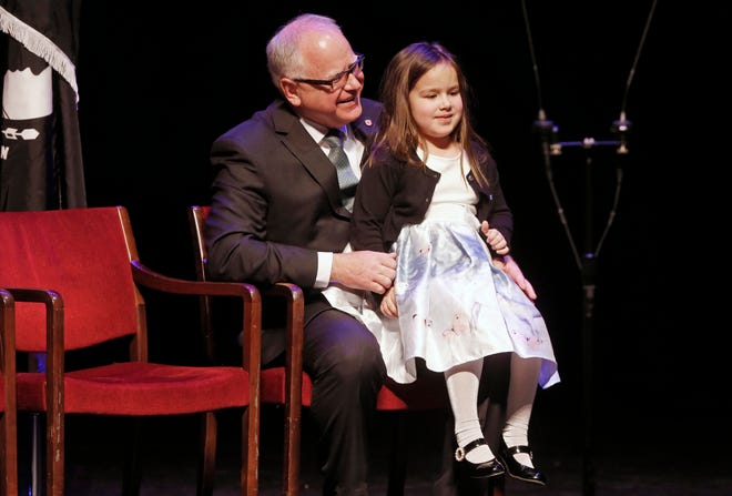 Minnesota Governor-elect Tim Walz holds the five-year-old daughter of newly elected Lt. Gov. Peggy Flanagan as she addresses those gathered for his Walz' swearing in moments later on Monday, Jan. 7, 2019, in St. Paul, Minn. (AP Photo/Jim Mone)