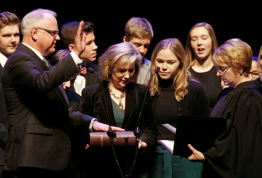 Minnesota Governor-elect Tim Walz, left, places his hand on the Bible held by his wife Gwen, center, as he prepares to take the oath of office administered by Supreme Court Chief Justice Lorie Skjerven Gildea, right, Monday, Jan. 7, 2019, in St. Paul, Minn. (AP Photo/Jim Mone)