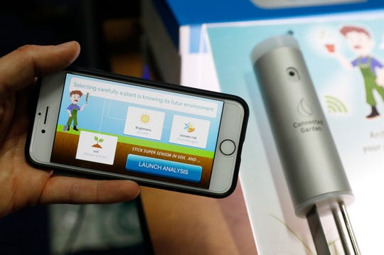 The Archibald e-gardener app, left, and Super Sensor, right, are on display at the Connected Garden booth during CES Unveiled at CES International, Sunday, Jan. 6, 2019, in Las Vegas. The Super Sensor, over a 24-hour period, can analyze the soil, brightness and climate and recommend types of plants according to preferences. The app has augmented reality and recommends care for specific types of plants. (AP Photo/John Locher)