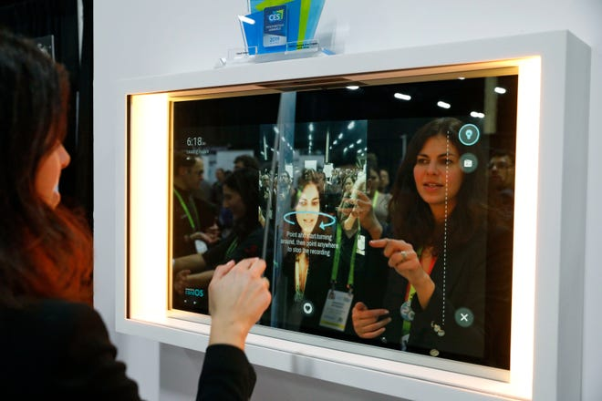 A woman demonstrates the Artemis smart mirror at the CareOS booth during CES Unveiled at CES International, Sunday, Jan. 6, 2019, in Las Vegas. The interactive mirror has video capture, virtual try-ons, facial and object recognition, and can give the user video instruction on specific makeup products, among other things. (AP Photo/John Locher)