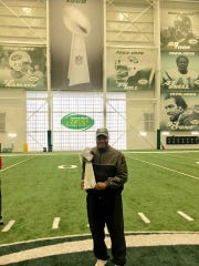 Former FAMU head coach Billy Joe poses with the Vince Lombardi Trophy from Super Bowl III at New York Jets' practice facility.