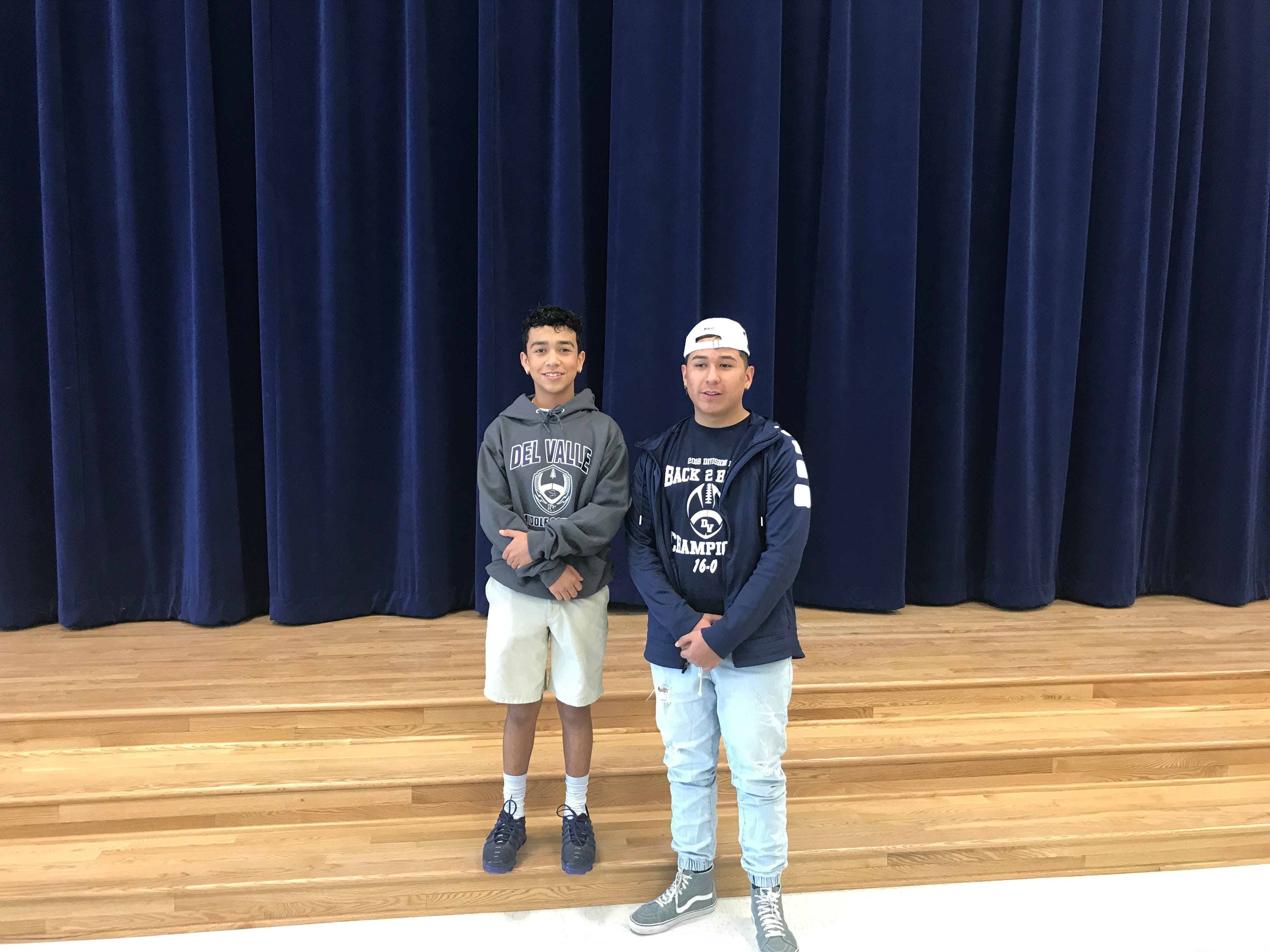 Eight graders R. J. Bracamontes and Jesus Ceniceros stand on the stage of the cafeteria of their new campus.