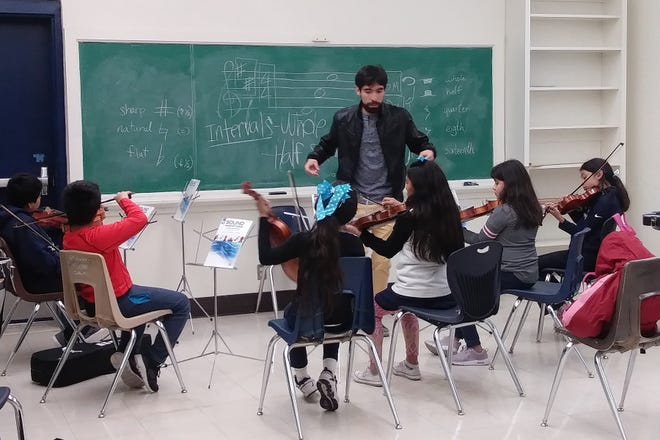 Octavio Macias leads students in the Tocando After-School Music Project.