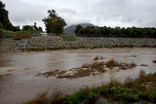 Water rushes through Calleguas Creek in Camarillo on Monday as rain falls in Ventura County.