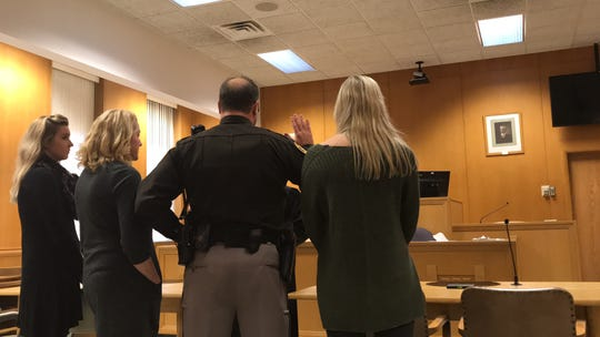 New Wood County Sheriff Shawn Becker takes the oath of office Monday afternoon in the Wood County Branch 1 Courtroom with his wife and two daughters by his side.