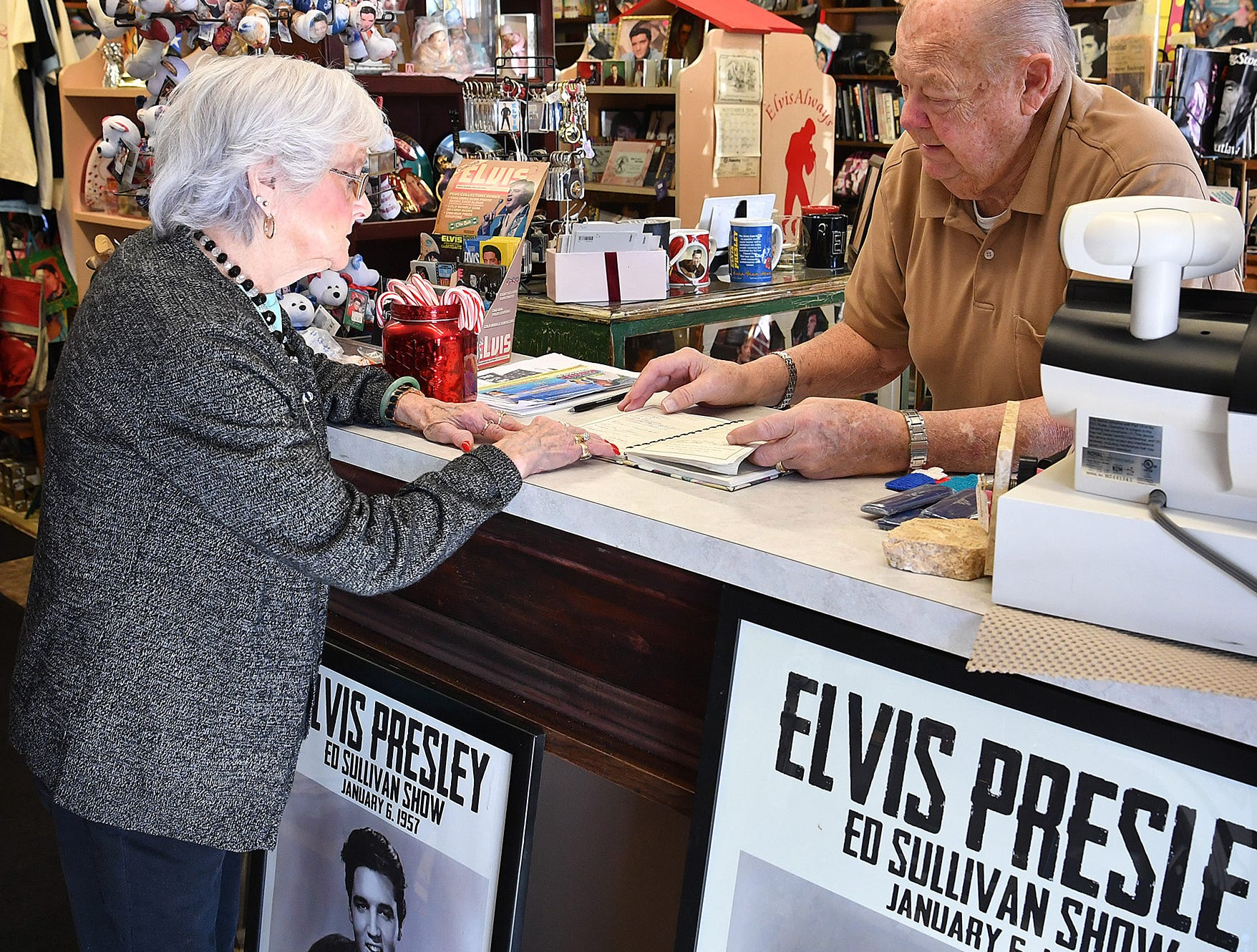 Wally and Margaret Waller look over the guest registry at their store, Elvis Always Gifts and Collectibles. Visitors from around the world have shopped in their store that celebrates the King of Rock 'n Roll.
