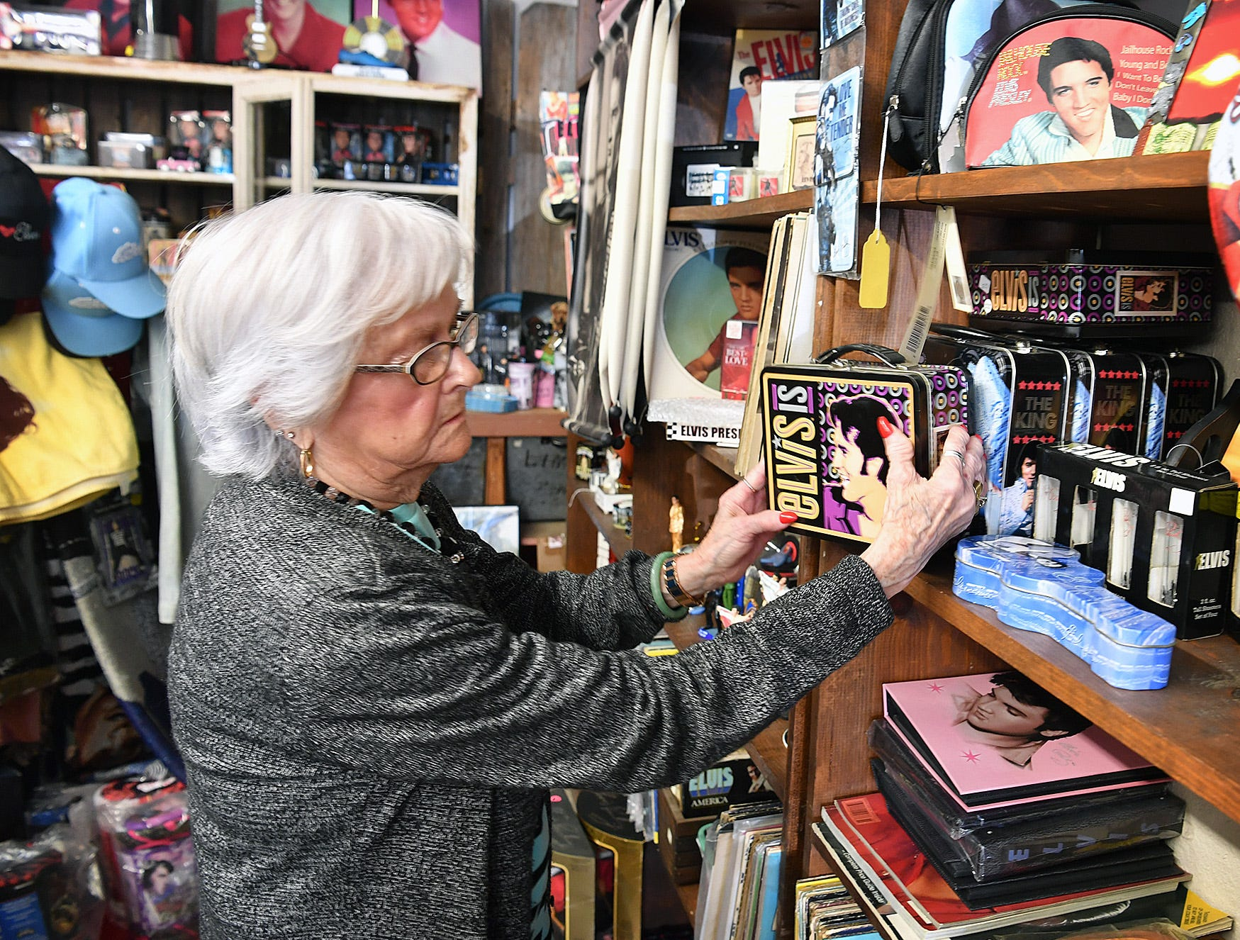 Margaret Waller, co-owner of Elvis Always Gifts and Collectibles store, arranges a display of Elvis lunchboxes.
