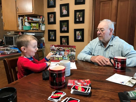 Wyatt and Grandpa Bob look at a family photo calendar.