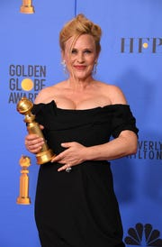 Patricia Arquette shows off the Golden Globe she won for her performance in Showtime's 'Escape at Dannemora.'