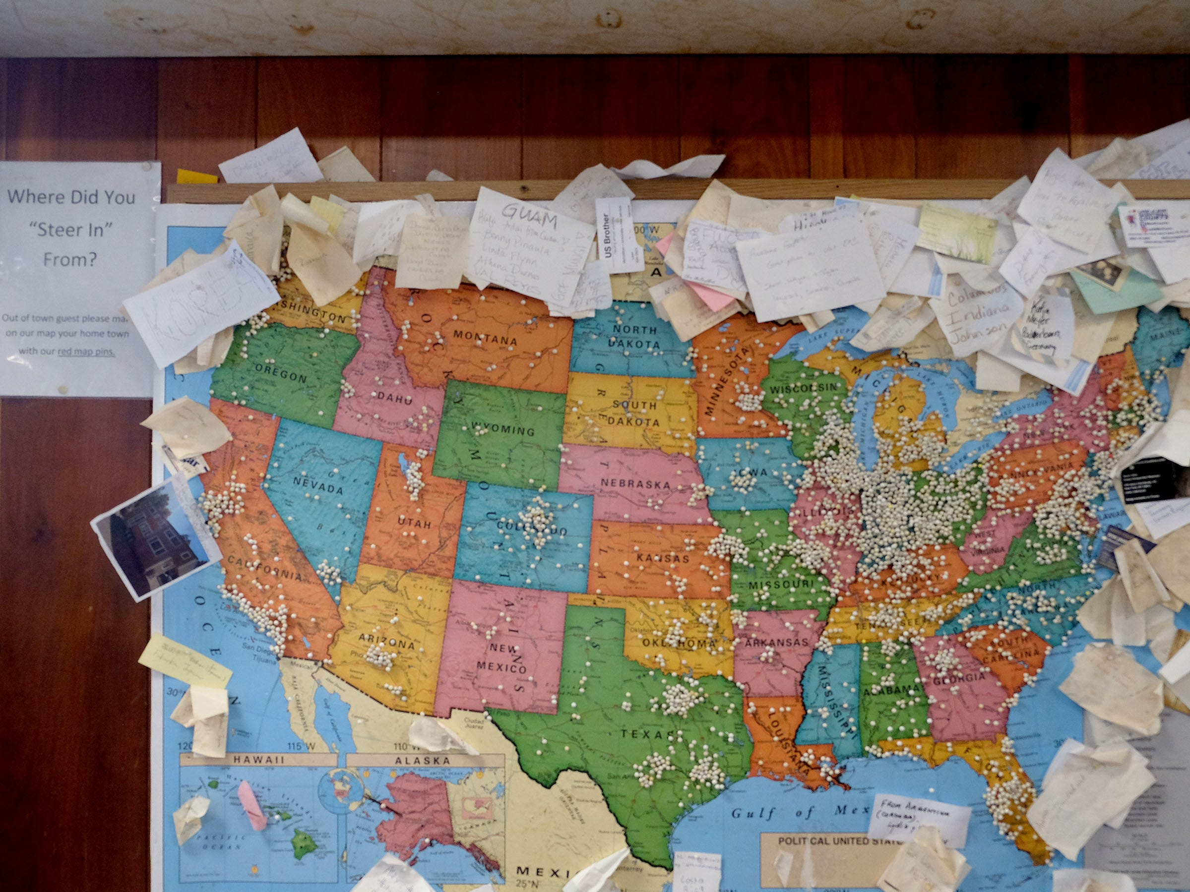 A bulletin board in the tiny lobby shows the distance visitors will travel to chow down at the Steer-In.