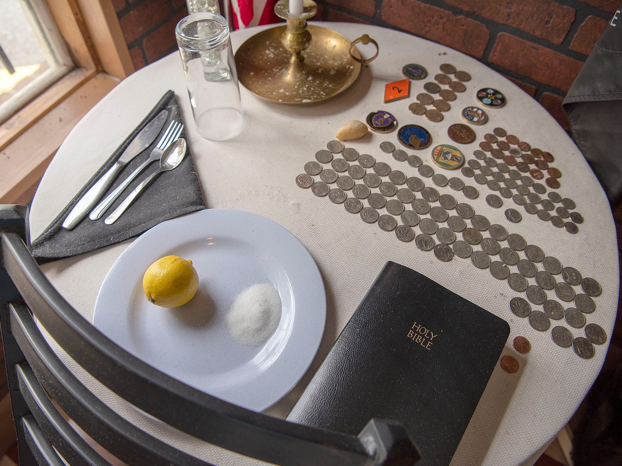 "The Missing Man Table at the Tin Plate honors military members missing in action as well as prisoners of war. The quarters were with fallen soldiers when they were killed. The display also includes ""challenge coins"" from military leaders."
