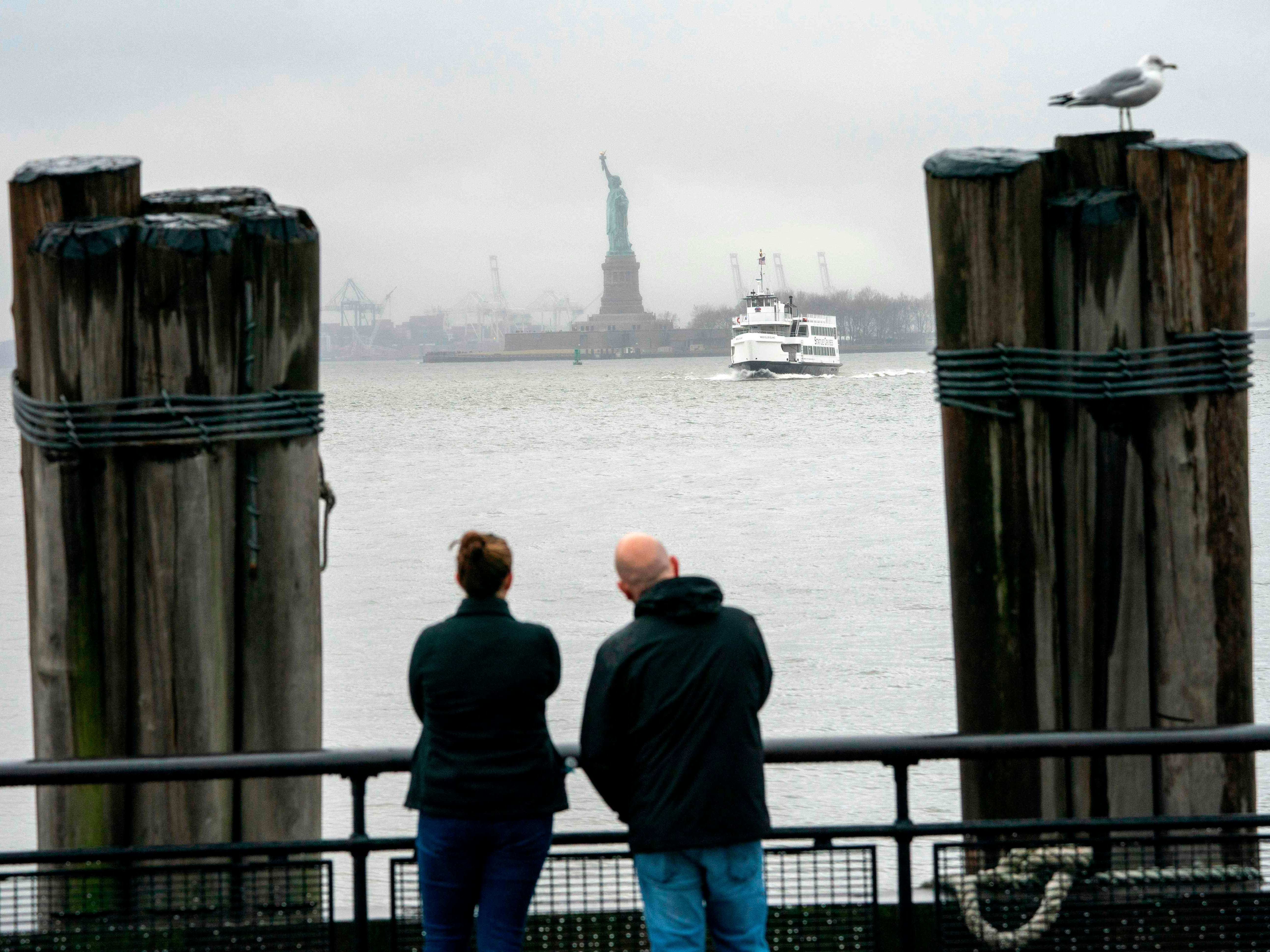 People watch as the Statue of Liberty and Ellis Island ferry transports passengers on Jan. 5, 2019, in New York, as the government shutdown enters its third week. New York state funds are being used to keep the attractions open during the shutdown which has affected National Parks.
