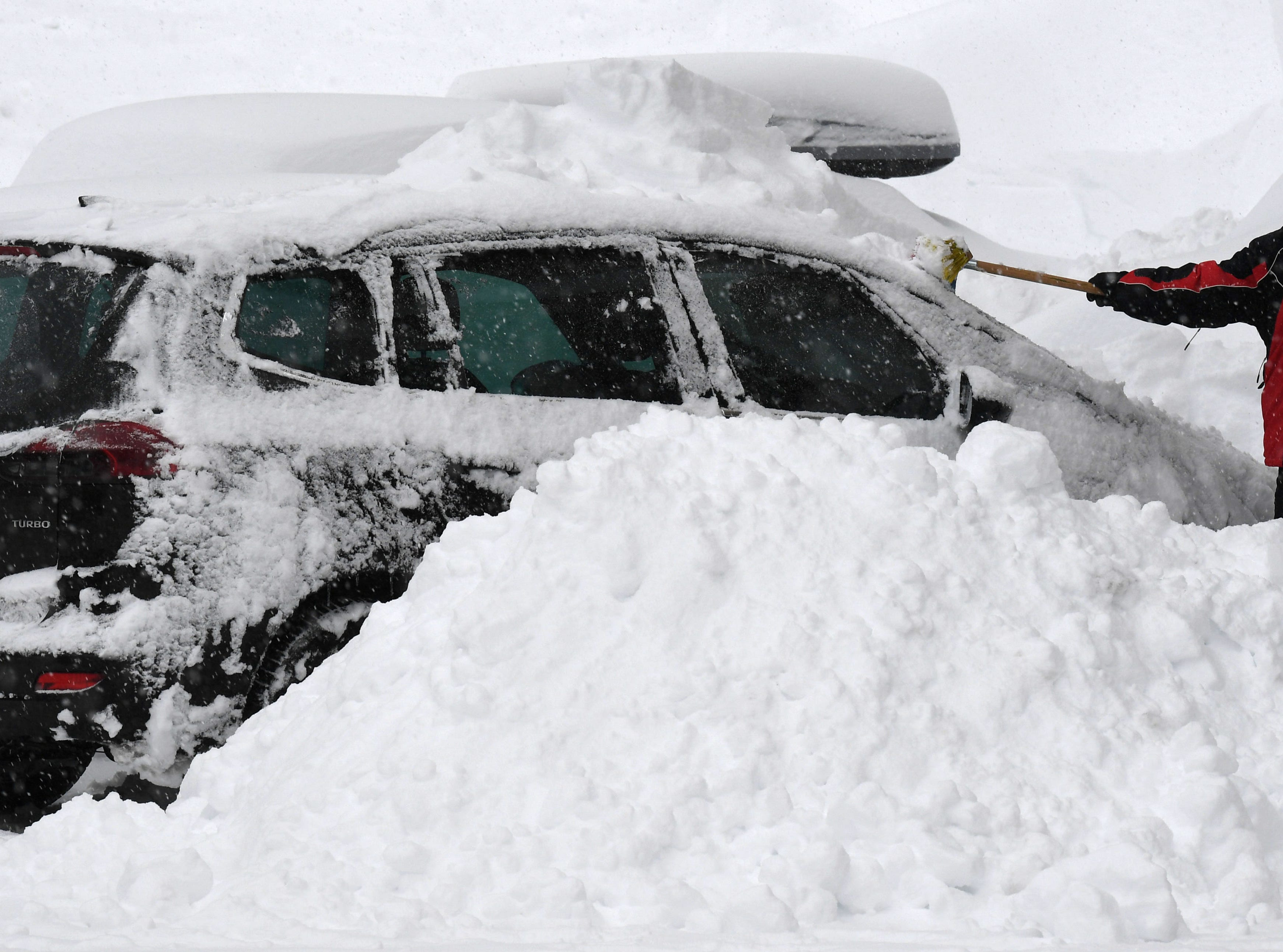 A man removes the snow from his car after heavy snowfall in the small village of Filzmoos, Austria, Jan. 7, 2019.