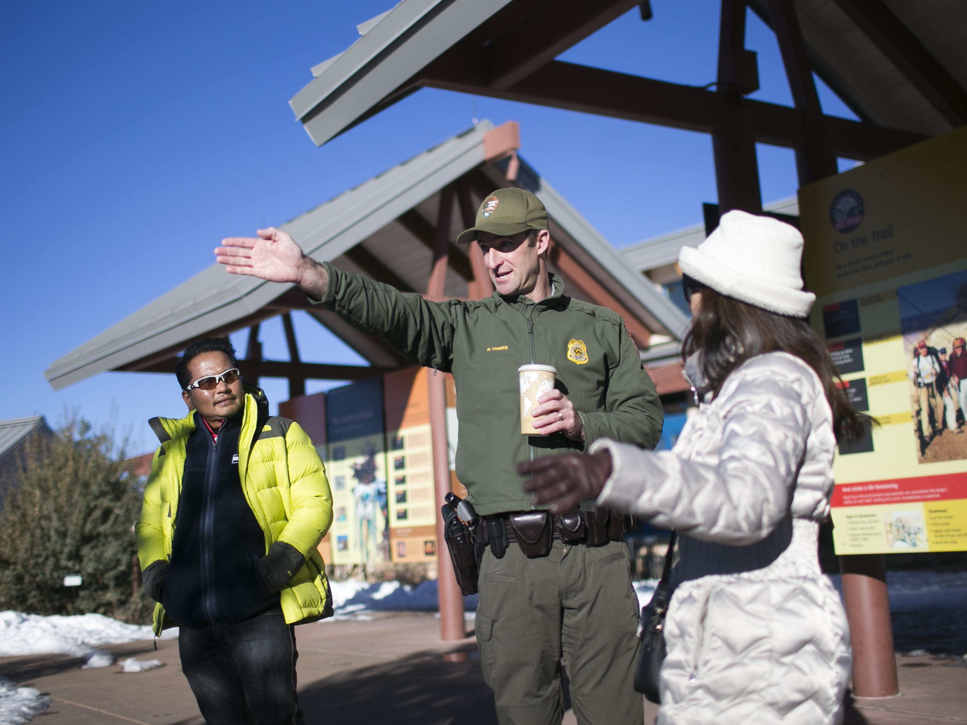 Brandon Torres (center), the Branch Chief of Emergency Services at Grand Canyon National Park, directs guests in the park on Jan. 4, 2019. The park was staffed at minimum capacity due to the government shutdown but retained much of its services due to an executive order issued by Arizona Governor Doug Ducey to run the park with state funds in the event of a shutdown.