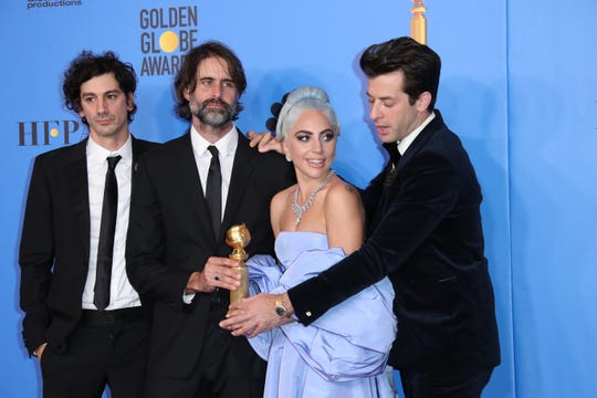 From left, Anthony Rossomando, Andrew Wyatt and Mark Ronson had to be careful not to tread on Lady Gaga's voluminous dress.
