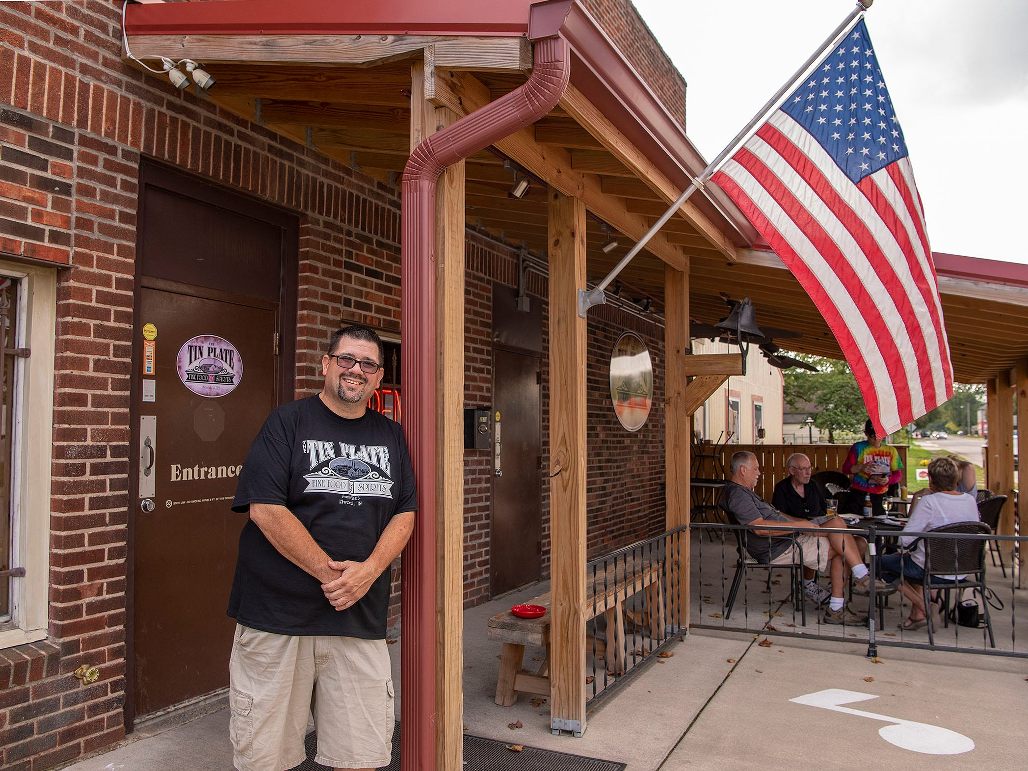 "Patrick Rice Jr. stands outside the Tin Plate restaurant in Elwood. The building was constructed in 1916 and served mainly as a watering hole for workers at the hot mill tin factory across the street. Rice and family members helped renovate the building into the restaurant, which opened in 2015. ""Our hard work paid off,"" he says. ""It goes to show that you can do it, man. The American dream – it's out there."""