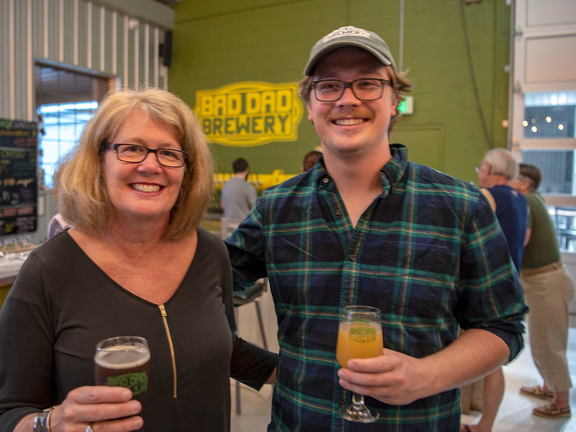 Grains & Grill co-owner Joanie Howard and son, brewer Patrick Howard, stand in the tasting room of Bad Dad Brewery, located inside the restaurant. The brewery has a dozen taps featuring beer made on site.