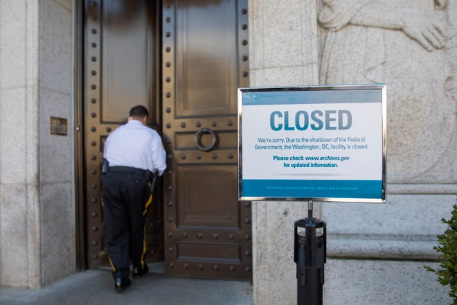 A guard enters the closed National Archives building in Washington, DC on Dec. 22, 2018. A partial US government shutdown began at midnight, Dec. 22, when a funding agreement between Congress and President Trump could not be reached.