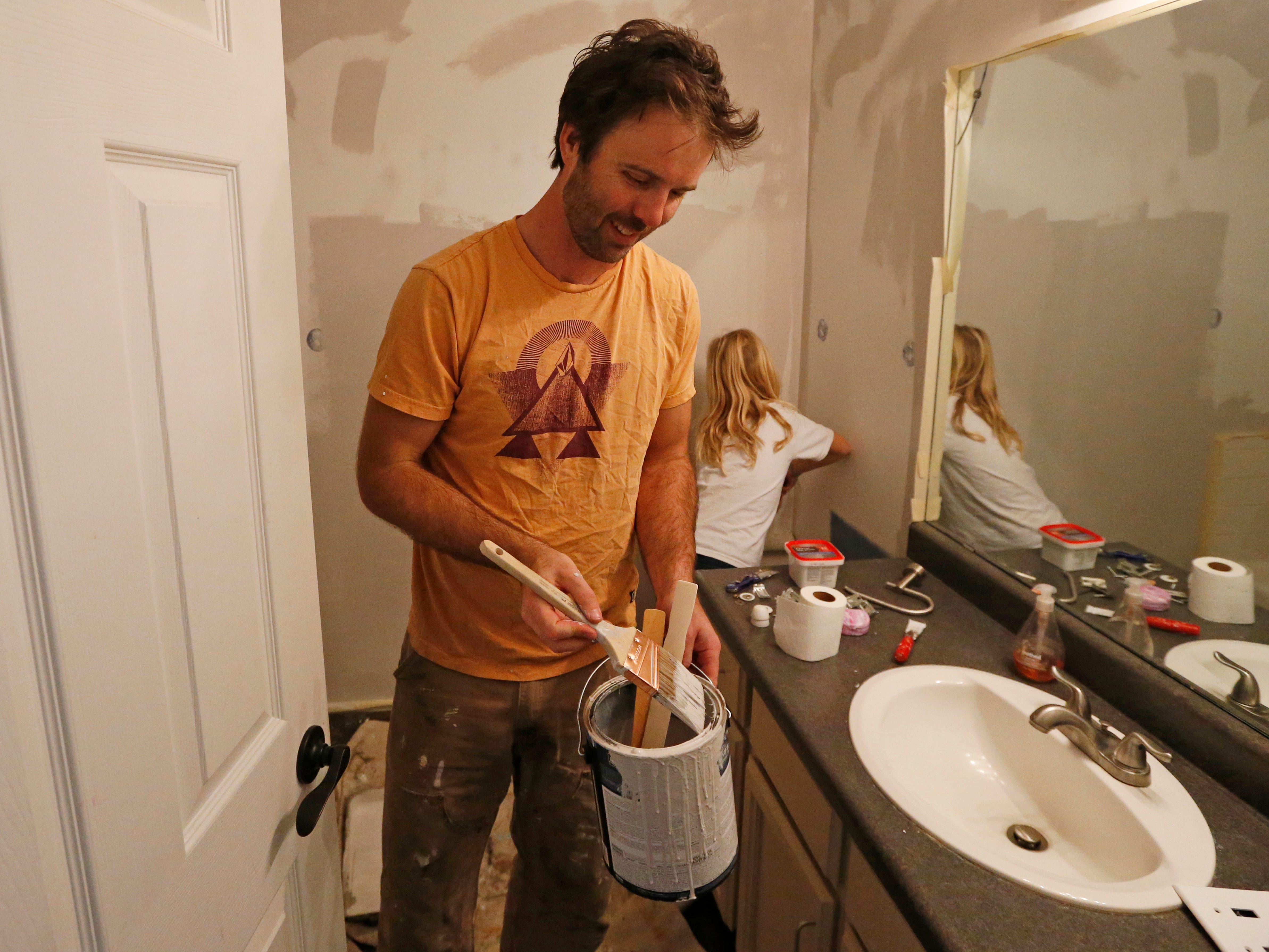 Federal contractor Chris Erickson paints his bathroom, Jan., 4, 2019, in North Salt Lake, Utah. Erickson says he'll run out of vacation days if the shutdown continues. The father of three from Salt Lake City will then crack into his savings, and he'll likely postpone a 14th wedding anniversary trip with his wife to a cabin. Erickson said he likely won't get the chance for reimbursement for the lost days because he's a contractor.
