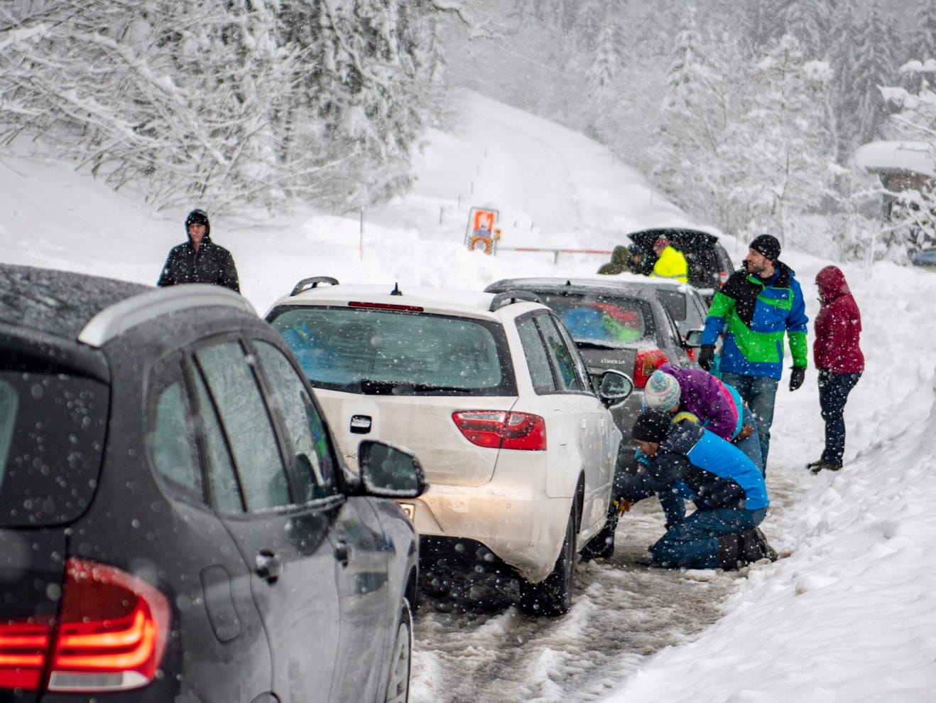 People put on snow chains in front of a closed road and a multi-language sign warning of the 'danger of avalanches' during heavy snowfall near Untertauern, Austria, Jan.7,  2019.