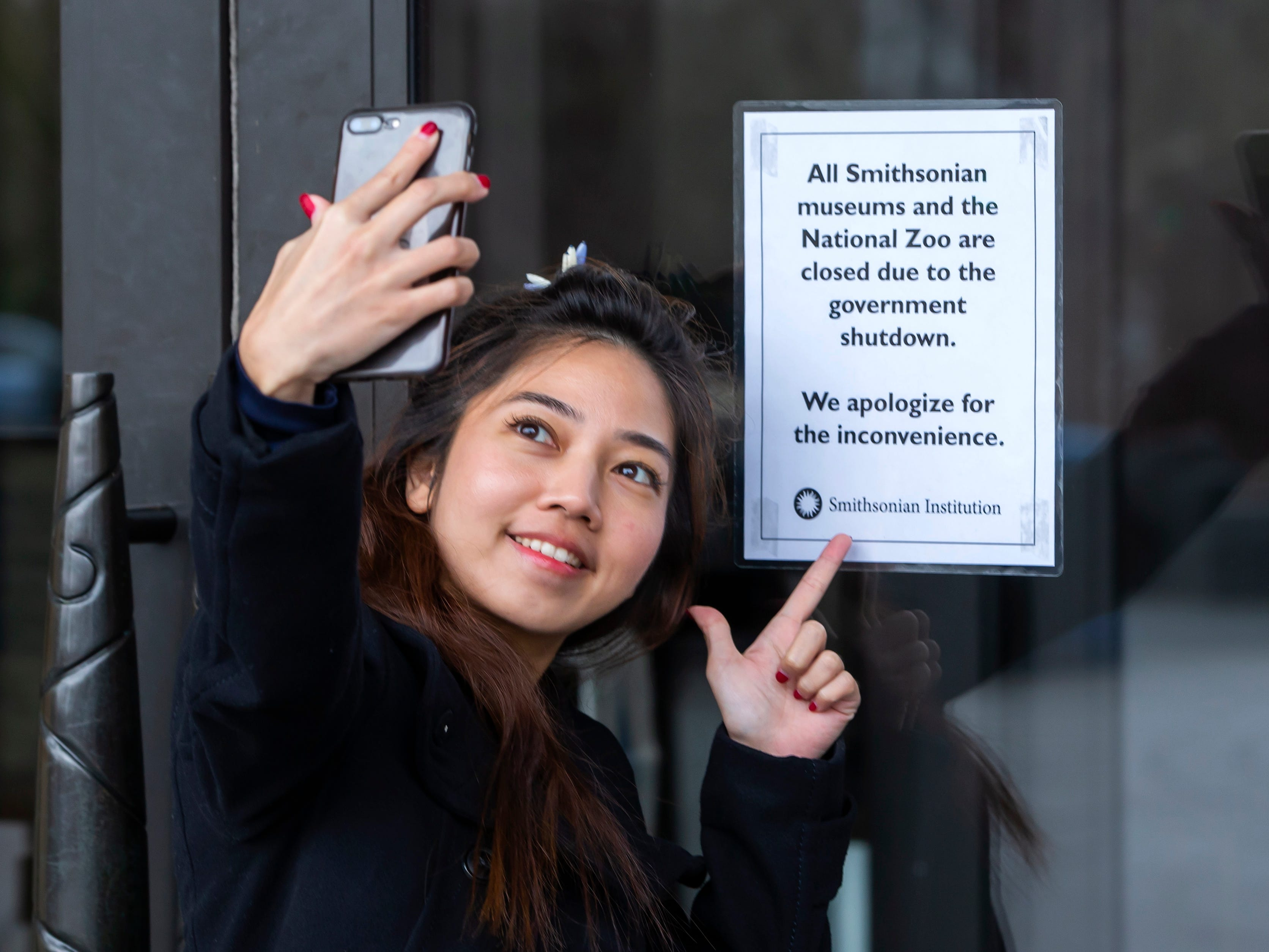 Kunyanatt Chalothorn from Thailand takes a selfie with a closure sign at the entrance to the Smithsonian American Indian Museum in Washington, DC on Jan. 2, 2019.
