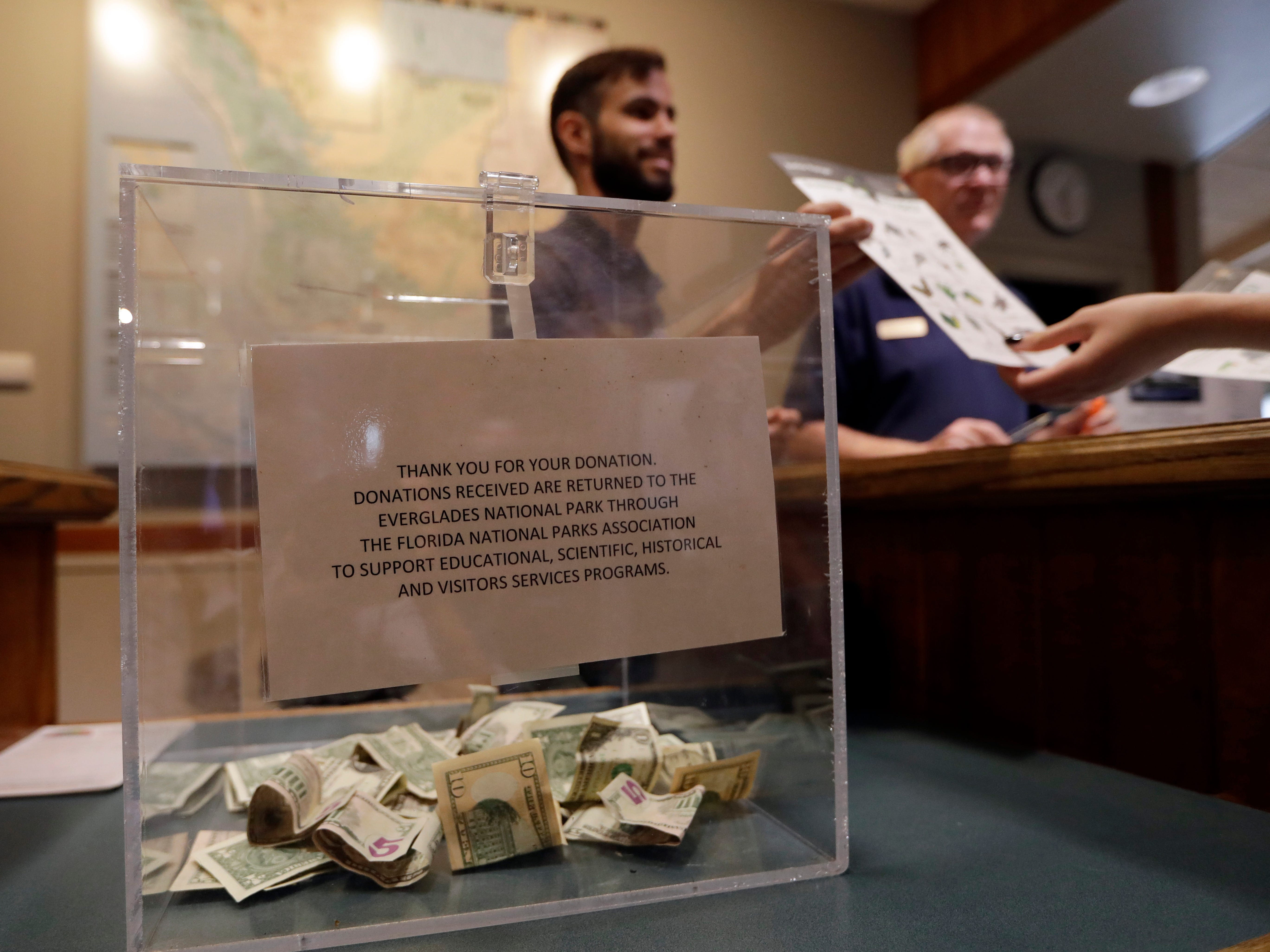 A donation box sits on the counter as Dany Garcia speaks with visitors at the Ernest F. Coe Visitor Center in Everglades National Park, Jan. 4, 2019, in Homestead, Fla. Garcia is being paid by the Florida National Parks Association to work in the center during the partial government shutdown. As the shutdown drags on, private organizations, local businesses, volunteers and state governments are putting up the money and manpower to keep national parks across the U.S. open, safe and clean for visitors.