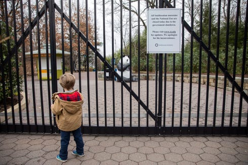 A disappointed young visitor, Asa Hazelwood, 3, pauses at the closed gates to the Smithsonian National Zoo in Washington, DC on Jan. 2, 2019. Asa's mother was unaware of the zoo's closure. The Smithsonian museums and the National Zoo are now closed to visitors during a partial shutdown as Congress and President Trump are at an impasse over funding of Trump's proposed southern border wall.