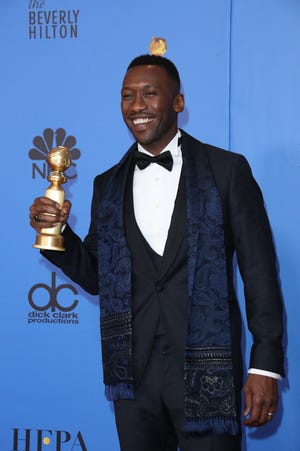 """Mahershala Ali poses with his Golden Globe for best supporting actor in a film for """"Green Book."""""""