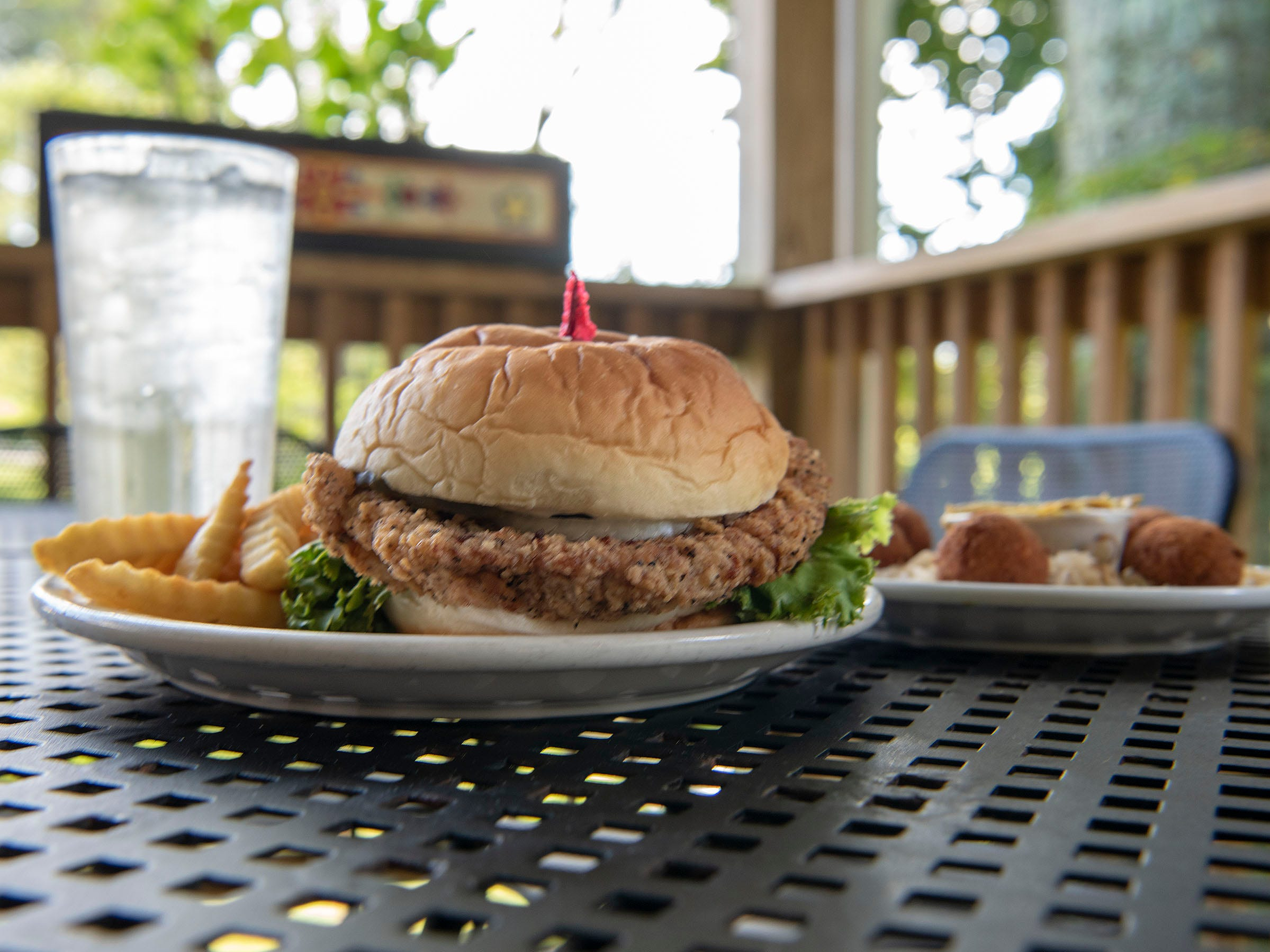 The pork tenderloin sandwich at the Brau Haus is punched up with a pleasing dose of pepper. It's featured here on the Brau Haus patio along with a serving of sauerkraut balls.