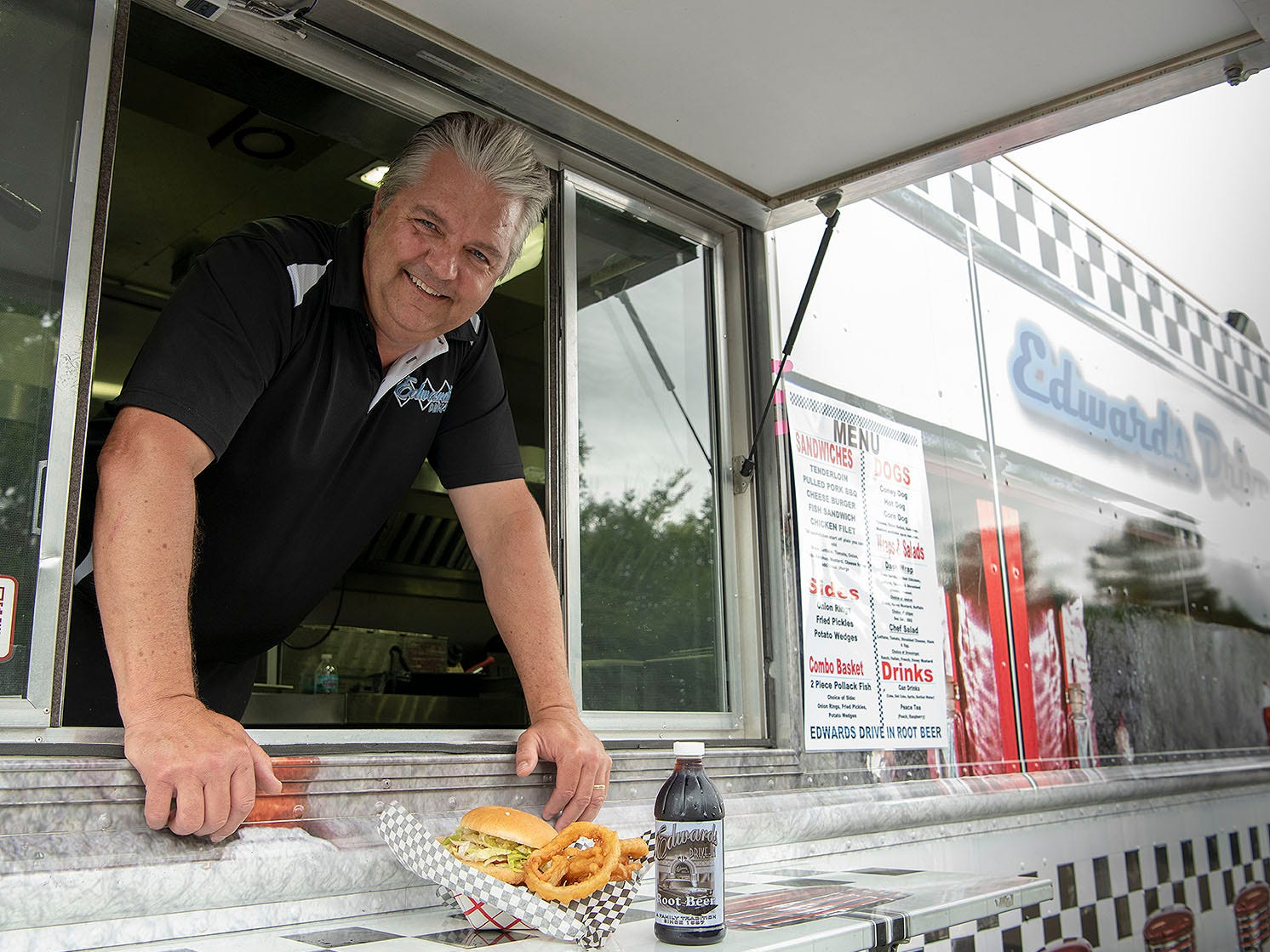 "Jeff Fisher poses with a pork tenderloin sandwich and house-made root beer in his food truck, Dashboard Diner, which is frequently seen around Indianapolis. Fisher also owns a catering business and the Edwards Drive-In, which has been open since 1957. ""The only thing we've never changed is the menu,"" he says."