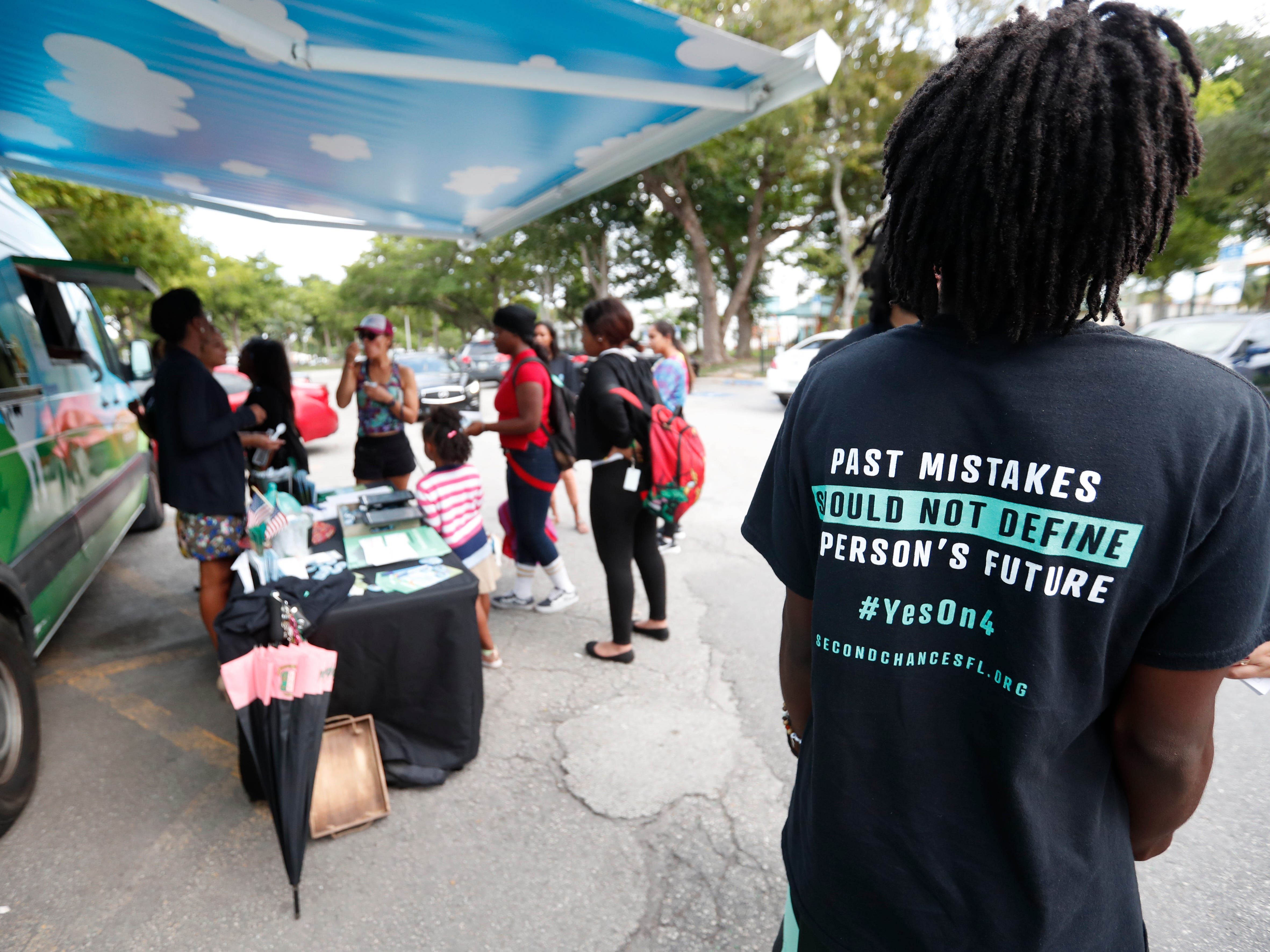 "In this Oct. 22, 2018 photo, people gather around the Ben & Jerry's ""Yes on 4"" truck as they learn about Amendment 4 and eat free ice cream at Charles Hadley Park in Miami."
