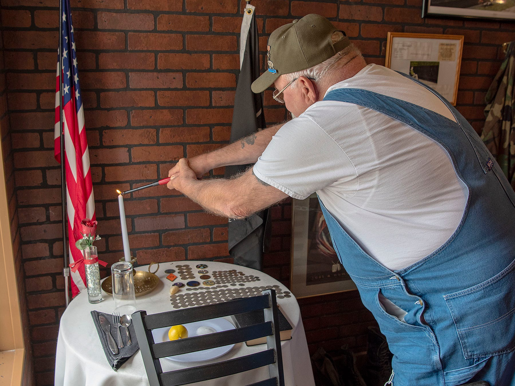 "Vietnam veteran Butch Lewis lights a candle at the Missing Man Table at the Tin Plate restaurant. Lewis, who served as a U.S. Army Airborne Ranger, said owner Patrick Rice asked him to help plan the memorial. ""We've had veterans come in and get down and pray right here at the table,"" Lewis said. ""It's really a moving thing."""