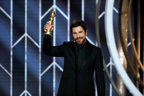 Christian Bale accepts the Golden Globe trophy for best actor for a musical or comedy during Sunday night's awards.
