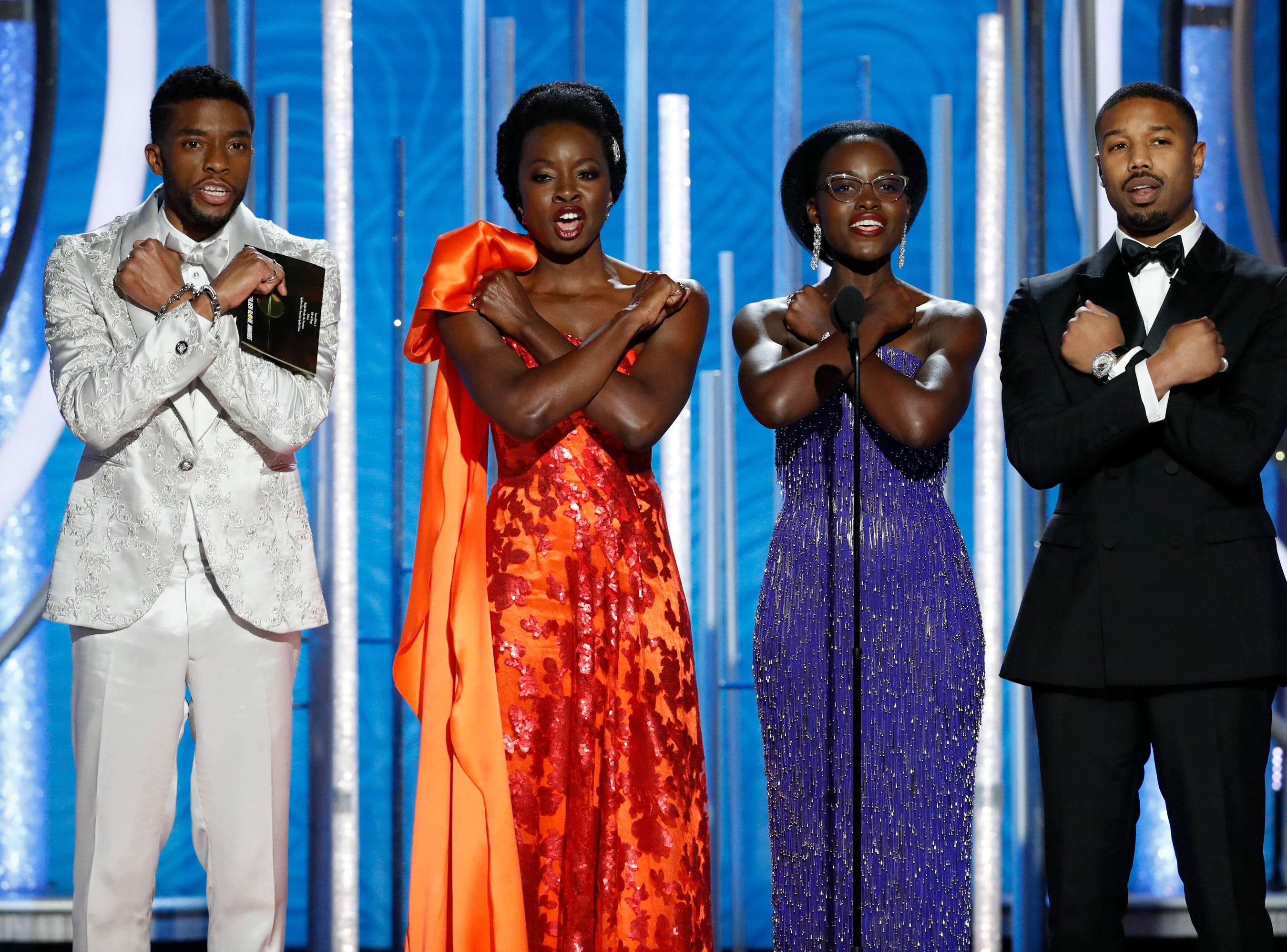 "This image released by NBC shows the cast of ""Black Panther,"" from left, Chadwick Boseman, Danai Gurira, Lupita Nyong'o and Michael B. Jordan doing the ""Wakunda Forever"" salute as they present the award for best animated feature during the 76th Annual Golden Globe Awards at the Beverly Hilton Hotel, Sunday, Jan. 6, 2019 in Beverly Hills, Calif. (Paul Drinkwater/NBC via AP) ORG XMIT: NYET621"