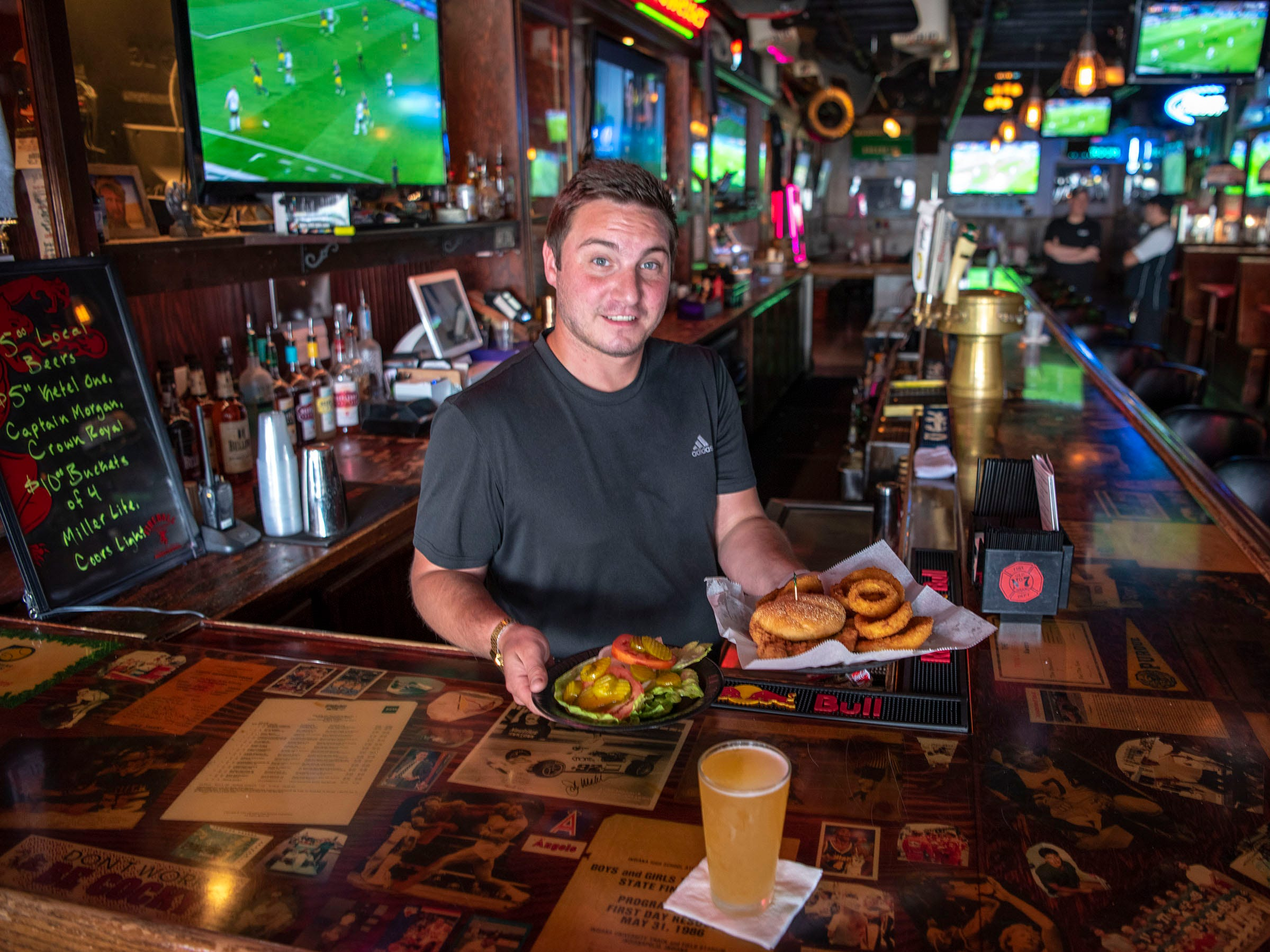"Dustin Stokes, bartender at Average Joe's Sports Pub & Grub, offers up a pork tenderloin sandwich and onion rings. Average Joe's has a reputation for fine tenderloins since being featured in the first season of Food Network's ""FoodNation with Bobby Flay"" in 2001."