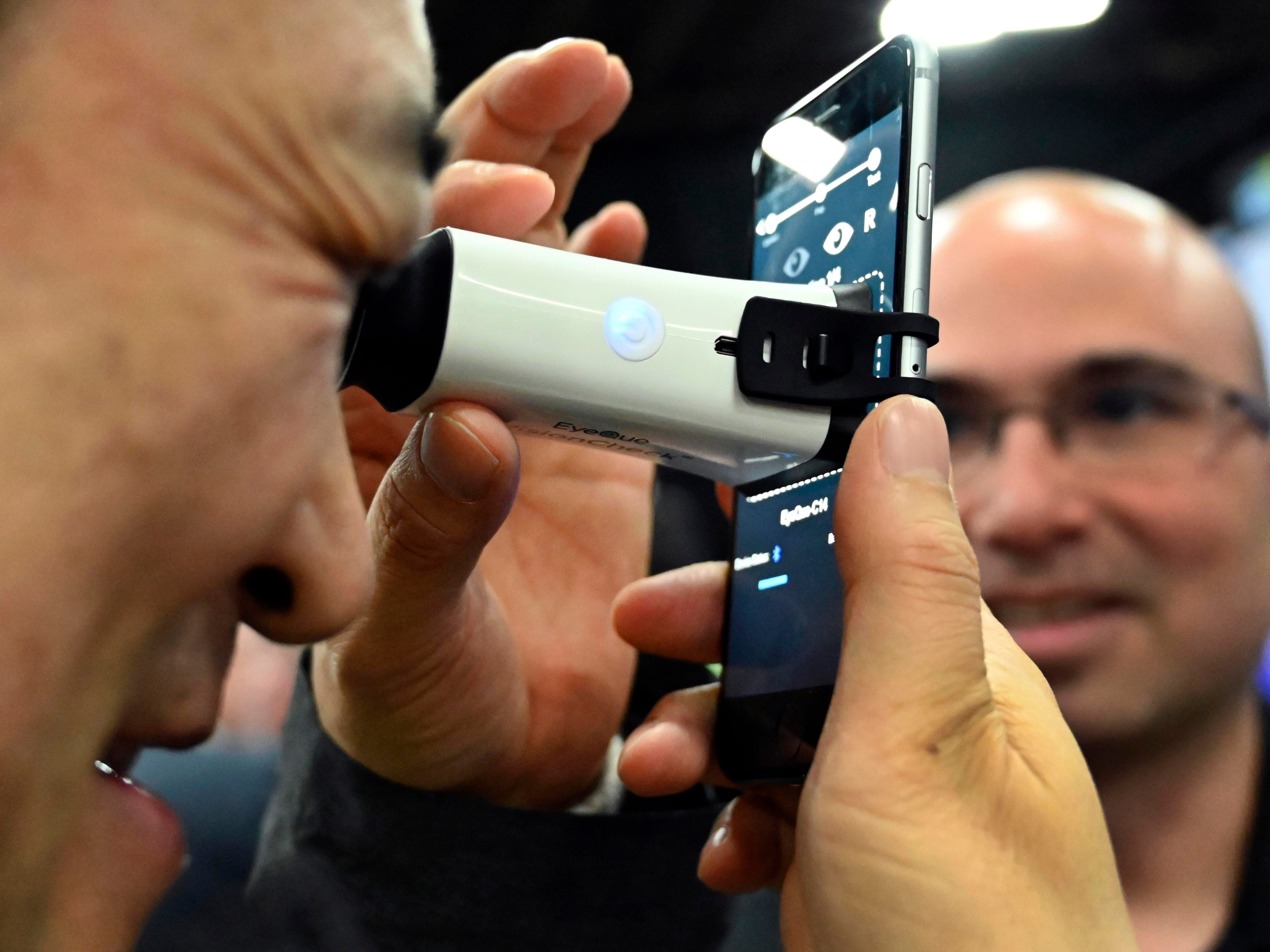 January 6, 2019; Las Vegas, NV, USA;  Norito Shimizu tries the EyeQue VisionCheck an at-home vision test device at CES Unveiled, a media preview event at the Mandalay Bay Convention Center. Right is EyeQue's Dr. Noam Sapiens. Mandatory Credit: Robert Hanashiro- USA TODAY NETWORK ORIG FILE ID:  20190106_ajw_usa_979.jpg